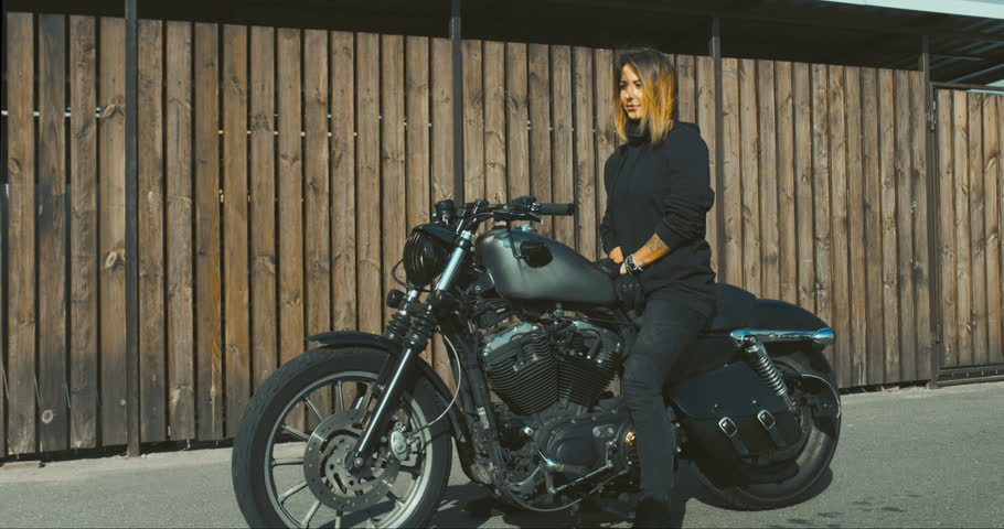 CINEMAGRAPH - seamless loop.Outdoor lifestyle portrait of sexy biker girl wearing leather jacket sits on a modern motorcycle. 4K UHD | Shutterstock HD Video #31165525