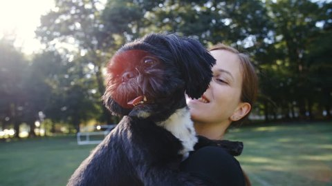 Dog and woman hugging while spinning in slow motion 4K. Close-up shot of cute black dog and woman in focus while turning around with sun flares in the frame.