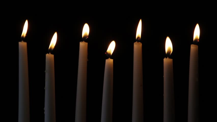 Looping. Seven tall white candles flicker in the darkness.