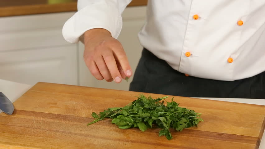 Cutting parsley and dill with a knife on wooden board #31220701