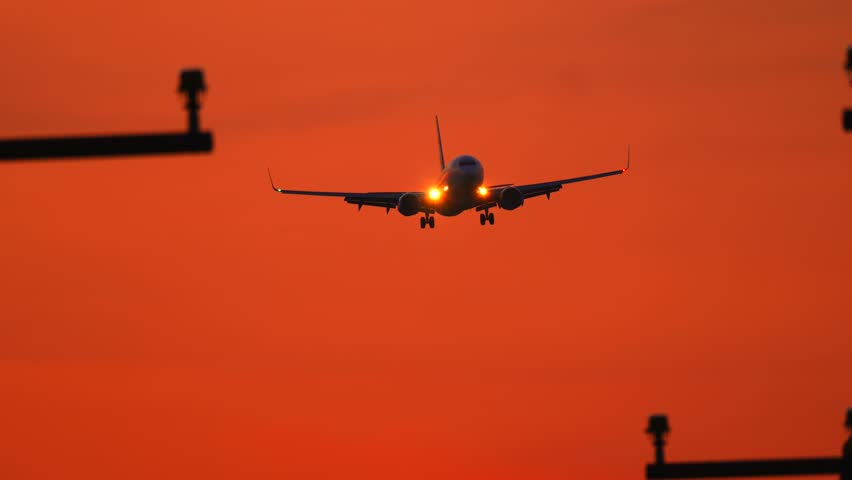Back view of a passenger airplane drifting down and landing on the jet airplane landing landing lights after sunset 4k stock footage clip mozeypictures Gallery