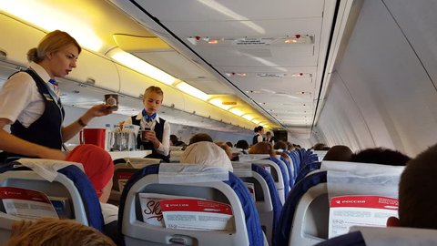 ROSSIYA AIRLINES FLIGHT, RUSSIA - CIRCA SEP 2017: Interior of airplane economy class cabin with passengers on seats. Flight attendants serves food and drinks to passengers on a Boeing 737-800.