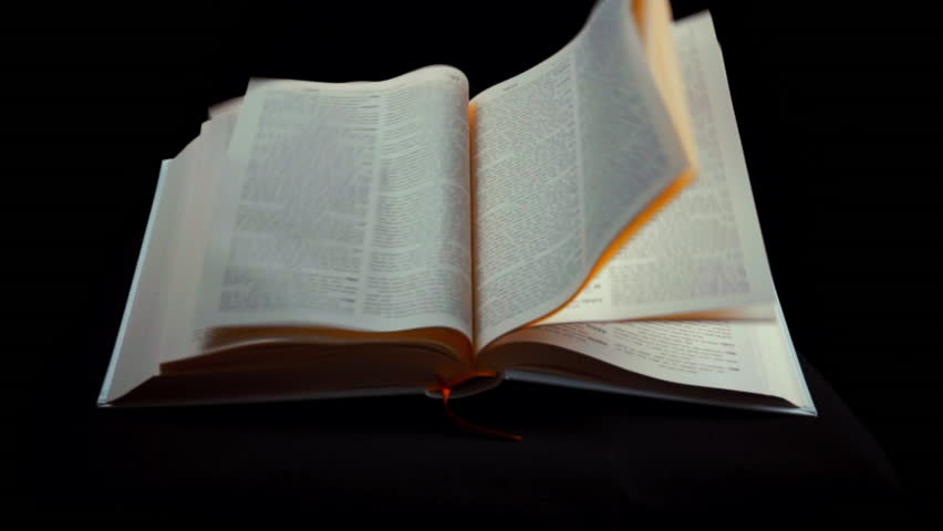 bible pages turning in the wind on black background in