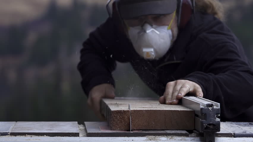 Wearing appropriate safety and protective gear (goggles, hearing protectors, dust mask) a woodworker starts a rip cut of a spruce plank using a tablesaw in an outdoor setting.