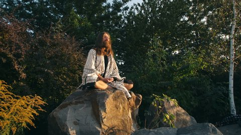 Yogi sitting on the rock and meditating