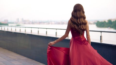 Beautiful woman in red fluttering dress. Urban background. Slow motion.