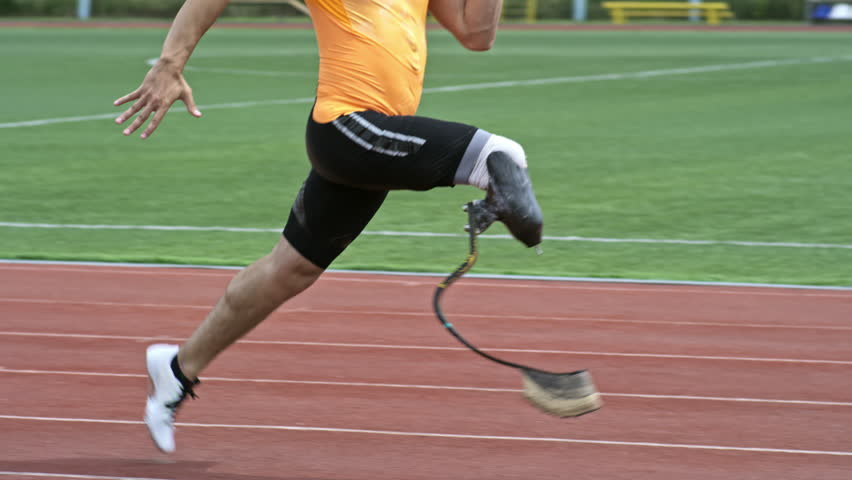 Slow mo side view of amputee athlete with prosthetic blade running on stadium track outdoors