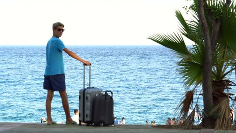young men on a tropical beach with suitcase