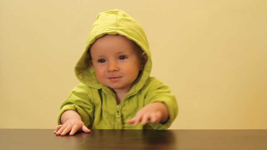 Little cute child with green hood practicing the stand up at the edge of the table