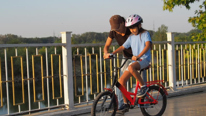 The child learns to ride a bicycle. Mother teaches her daughter to ride a bicycle.