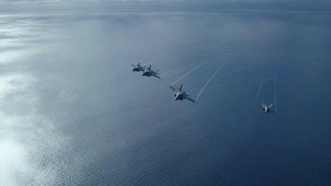 CIRCA 2010s - US Navy fighter jets fly over an aircraft carrier.