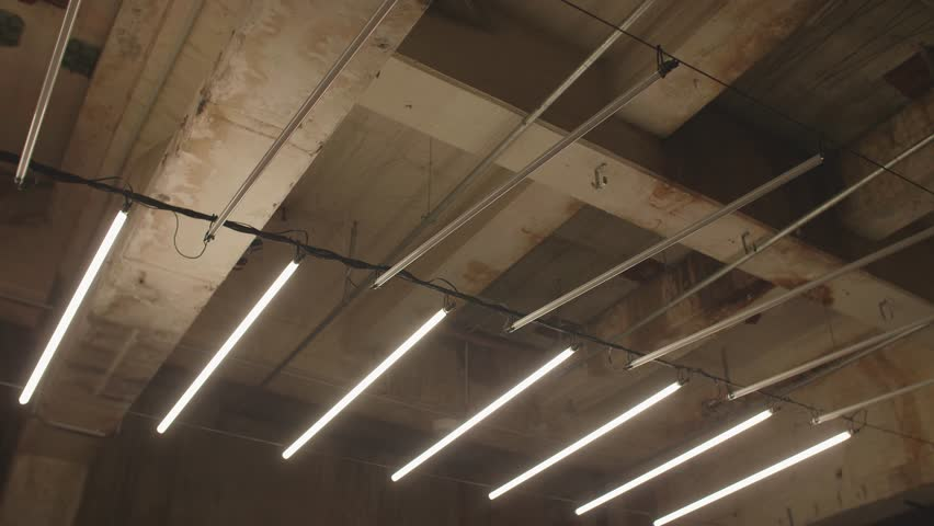 4k shot of white fluorescent lighting turn on and off and in industrial building. Many neon lights blinking and flashing on the ceiling. | Shutterstock HD Video #31374865