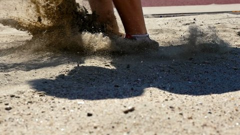 Close detail of sportsman legs doing long jump landing in sandpit, slow motion