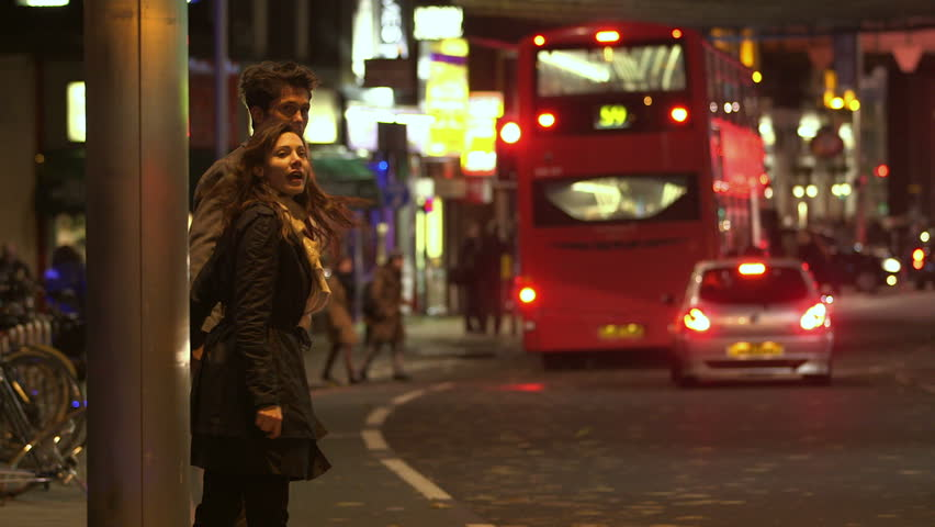 A man and a woman are holding hands as they walk across a busy London street at night. Many buses and cars and the bright lights of local businesses can be seen in the distance. #3138988
