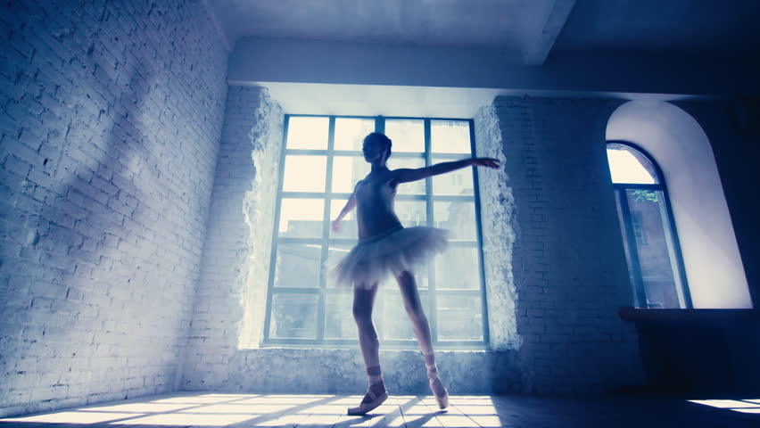 0bd9793980b Female ballet dancer performs Fouette at room with large window. Ballerina  night training.