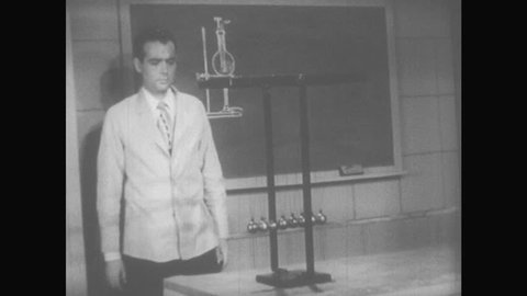 1950s: Man in suit approaches Newton's cradle, picks up leftmost ball and drops it. Newton's cradle in motion. Man stops motion in Newton's Cradle, and then resumes it.