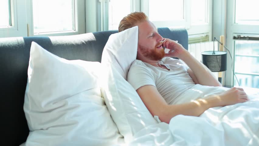 Young man talking over mobile phone while lying in bed | Shutterstock HD Video #31427515