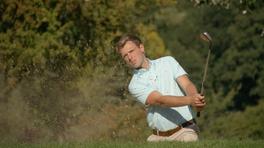 A Celebrating Golfer hits a golf ball out of a sand trap with exploding sand in slow motion, drops the ball into the cup and celebrates looking skyward.