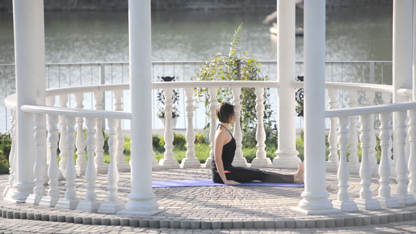A young yoga woman is practicing yoga in the park in the summer house in the summer house. | Shutterstock HD Video #31448395