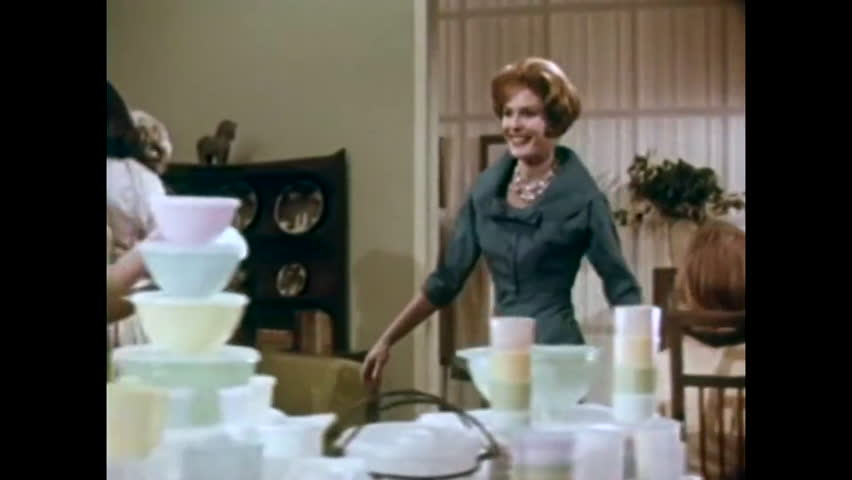 CIRCA 1958 - A hostess demonstrates Tupperware home products to guests at a party in a television commercial.