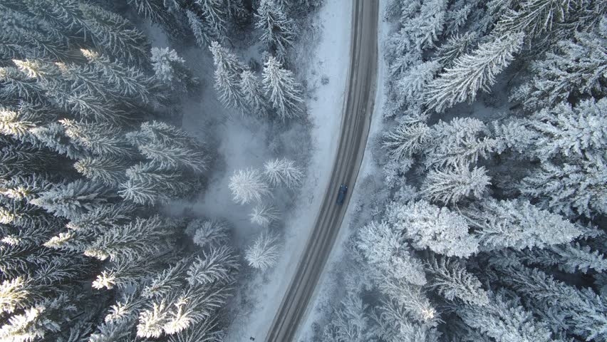 Car driving on winter country road in snowy forest, aerial view from drone in 4k.