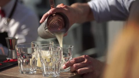 slowmotion shot of a bartender in an outdoor bar pours a cocktail into a glasses.