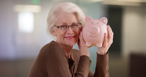Cheerful senior woman shaking piggy bank smiling at camera. Portrait of mature woman saving money holding up piggy bank indoors. 4k