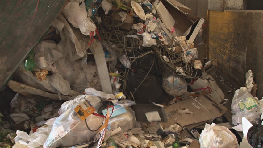 HOMER, AK - CIRCA 2011: Dumping a garbage truck of trash onto a conveyor to the
