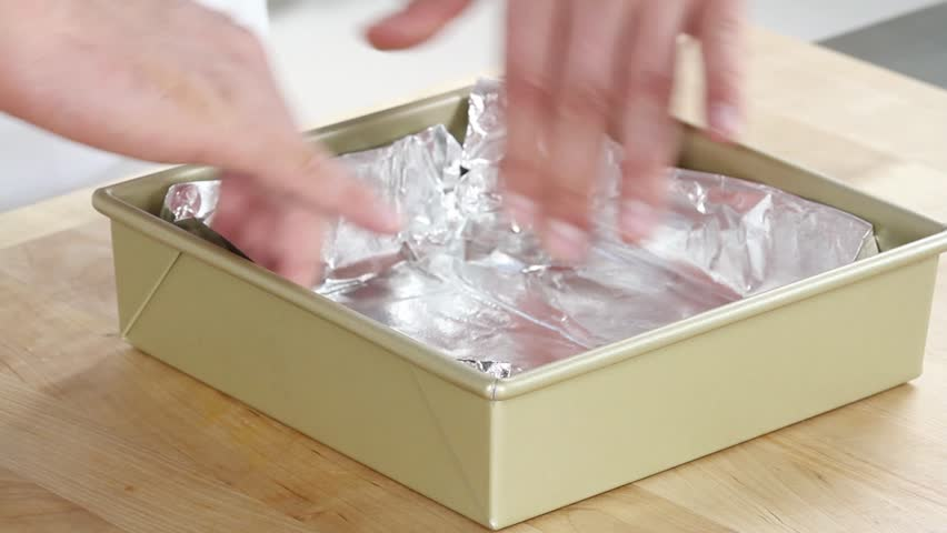 A baking tin being lined with aluminum foil