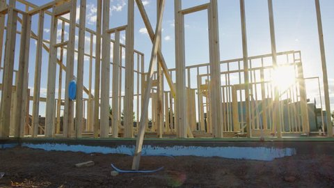 Move Left and Enter Residential Framed Home. view moves left as sun flare wraps around the beams of the new residential home framing wood walls