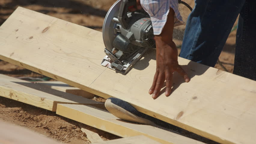 Worker Cuts Wood Sections Using Foot as Leverage. a construction worker quickly cuts wood using his foot as leverage.