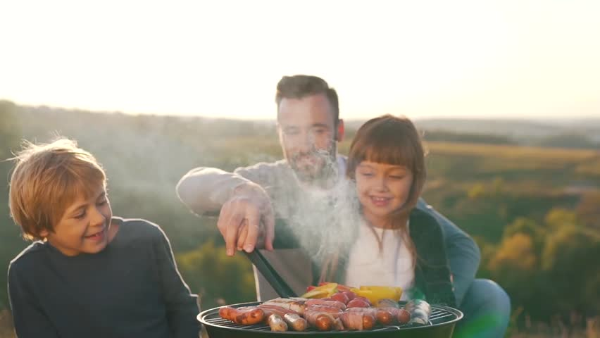 Father with children cook sausages on grill.