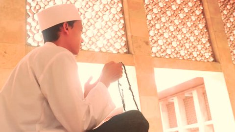 Video footage of a religious muslim person doing dhikr in the mosque while holding a praying beads