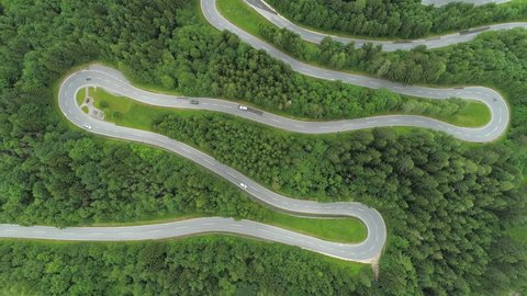 AERIAL, TOP DOWN: Motorcycles and cars driving on scenic zig zag winding road through lush dense spruce forest on mountain slope. Curvy switchback highway with hairpin turns snaking through the woods