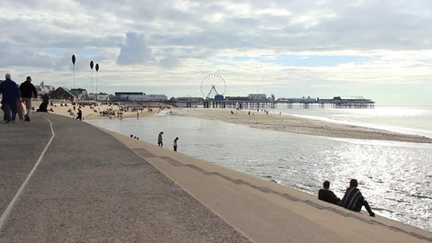 People walking the promenade and sitting on the steps of Blackpool Sea Defenses. View  towards the Central Pier. England, Lancashire, Blackpool.