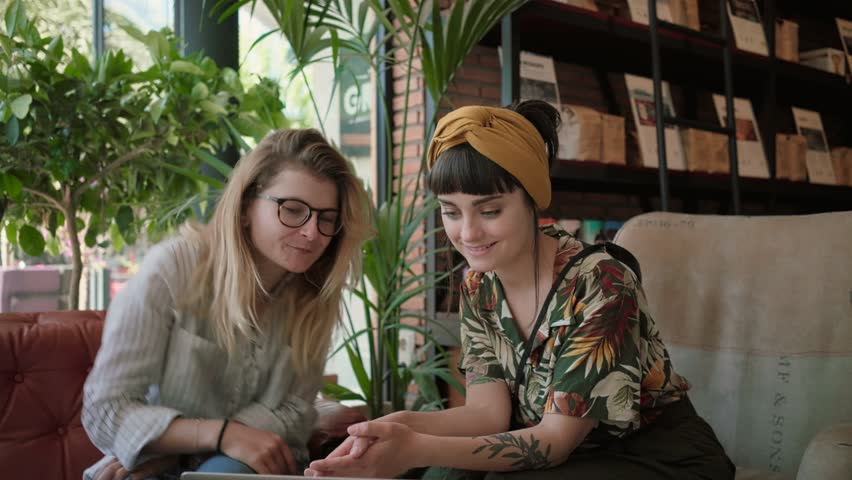 Two beautiful women, brunette and blonde, digital natives, millennial hipsters use video chat application on laptop inside busy trendy cafe, talk and have conversation with family or friends | Shutterstock HD Video #31582465