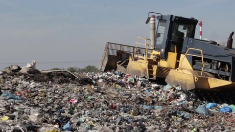 Bulldozer (tractor) moves non biodegradable garbage at landfill .