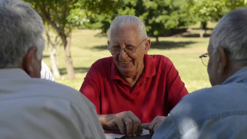Active retirement, old people and seniors free time, group of four elderly men having fun and playing cards game at park. Sequence of closeup, medium and wide shots