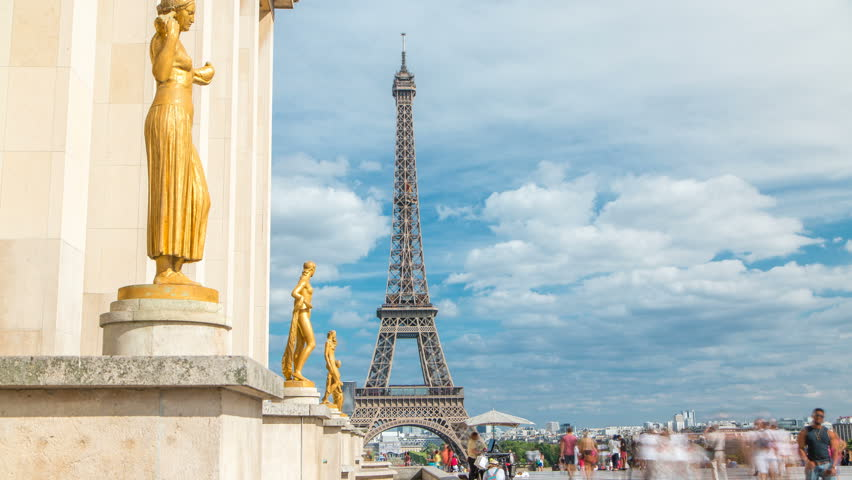 Eiffel Tower and the golden statues of women in the sun light timelapse, Trocadero square, Paris, France. Blue cloudy sky at summer day