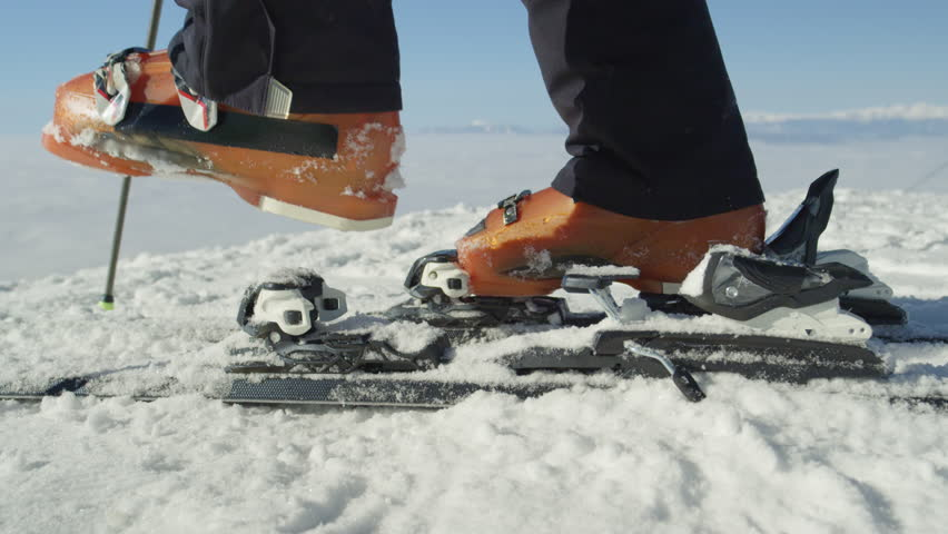 SLOW MOTION CLOSE UP: Skier stepping into the ski bindings with his ski boots on a sunny morning to start skiing. On sunny magical cold winter weather at ski resort in the Alps, Europe