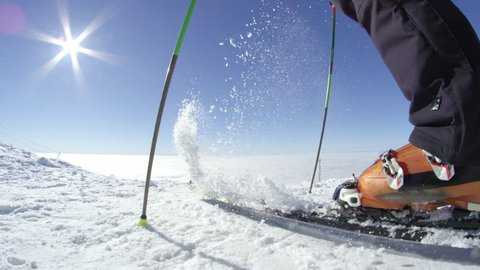 SLOW MOTION FISHEYE: Recreational skier removes freshly fallen snow from his skis on a top of the mountain above fog. Located at European ski resort in the Alps on a sunny cloudless winter day