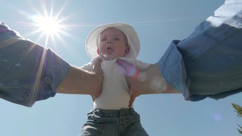 Cute baby child lift up by parent hands, kid close to the sky, sun shinning