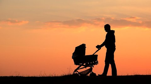 Father silhouette pushing baby pram on hill close colored sunset sky, magical