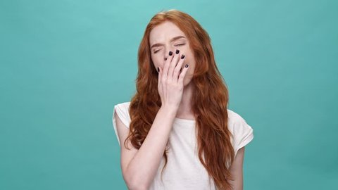 Bored ginger woman in t-shirt yawns and looking at the camera over turquoise background