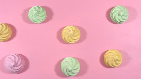 Pop Art Color style meringues bakery goodies on bright colorful background, overhead time lapse.