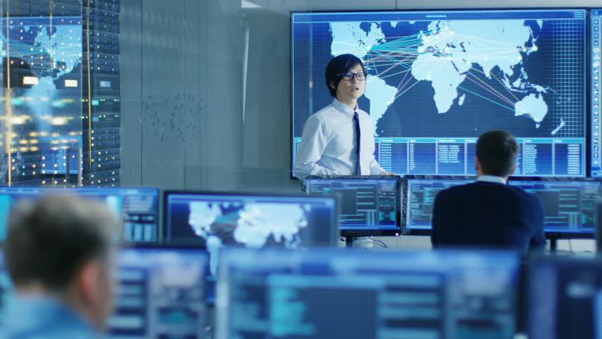 In the System Control Room Manager Holds a Briefing for His Staff Member. They're Work in Data Center and are Surrounded by Multiple Screens Showing Maps, Logistics Data. Shot on RED EPIC-W 8K #31689625