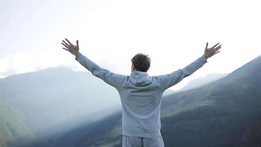 Man raises hands up standing back on mountain top morning sun shine slow motion. No face male silhouette figure in sportswear enjoy life wanderlust world. Achievement success motivation winner concept
