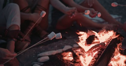 Close-up of young multi-ethnic friends sitting around bonfire and roasting marshmallows during camping trip