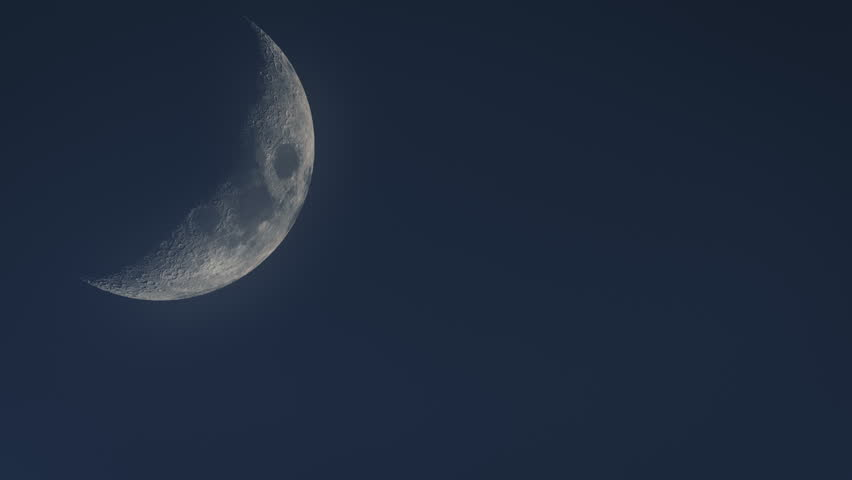 Close up of huge crescent moon traversing evening sky time lapse