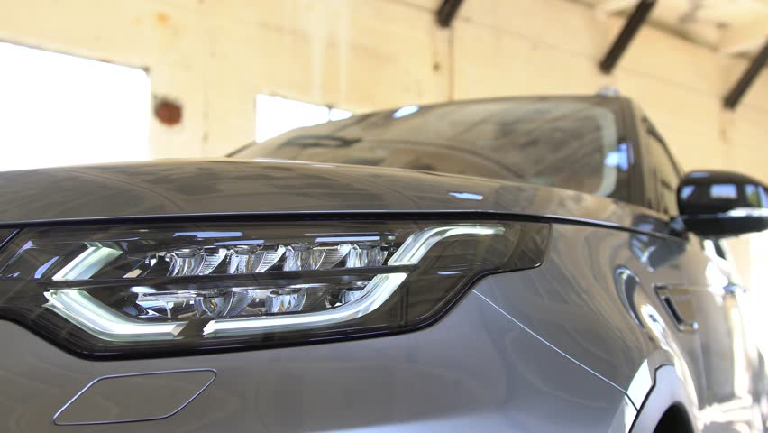 Detailed close up view of contemporary grey car headlight. Panning effect. | Shutterstock HD Video #31712545